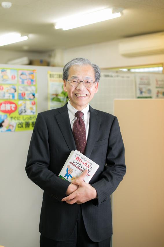 本を持つ川越雄一所長